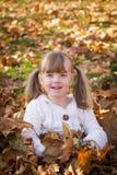 Petite fille jouant dans des feuilles de pile de feuille Image stock