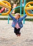 Petite fille jouant dans la cour de jeu Images libres de droits