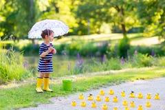 Petite fille jouant dans la forêt et les bottes de port Image libre de droits