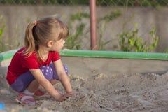 Petite fille jouant dans le bac à sable un jour ensoleillé d'été Image stock