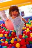 Petite fille jouant dans le château de rebondissement gonflable photos stock