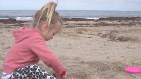 Petite fille jouant dans le sable sur la plage clips vidéos