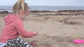 Petite fille jouant dans le sable sur la plage banque de vidéos