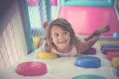 Petite fille jouant dans le terrain de jeu Fille caucasienne se situant dans le playr Photographie stock libre de droits