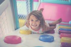 Petite fille jouant dans le terrain de jeu Mensonge et regard caucasiens de fille Images stock