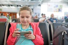 Petite fille jouant des jeux sur le smartphone dans le hall d'aéroport Image libre de droits