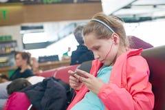 Petite fille jouant des jeux sur le smartphone dans le hall d'aéroport Photos libres de droits