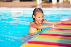 Petite fille jouant et ayant l'amusement dans la piscine avec le tapis d'air Photo libre de droits