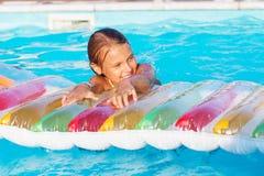 Petite fille jouant et ayant l'amusement dans la piscine avec le tapis d'air Images stock