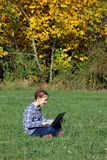 Petite fille jouant l'ordinateur portable en parc Image libre de droits