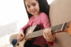 Petite fille jouant la guitare ? la maison Étude des notes de musique image stock