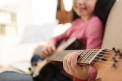 Petite fille jouant la guitare ? la maison Étude des notes de musique images libres de droits