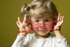 Petite fille jouant le jeu de berceau de chats images libres de droits