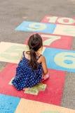 Petite fille jouant le jeu de marelle/petite fille jouant le jeu de marelle sur le terrain de jeu Photographie stock