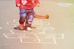 Petite fille jouant le jeu de marelle sur la rue Photographie stock