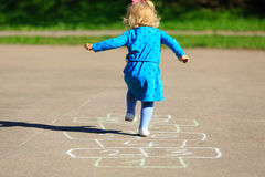 Petite fille jouant le jeu de marelle sur le terrain de jeu Photos libres de droits