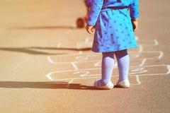 Petite fille jouant le jeu de marelle sur le terrain de jeu Images stock