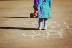 Petite fille jouant le jeu de marelle sur le terrain de jeu Photos stock