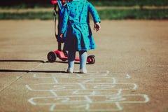 Petite fille jouant le jeu de marelle sur le terrain de jeu Images libres de droits
