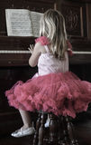 Petite fille jouant le piano Photographie stock