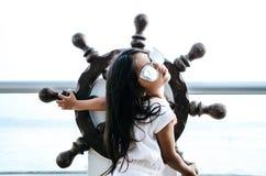Petite fille jouant pour être un marin sur un balcon avec un gouvernail de direction de bateau photographie stock