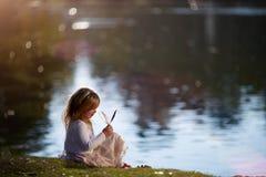 Petite fille jouant sur la berge Photographie stock