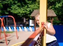 Petite fille jouant sur la cour de jeu photos stock