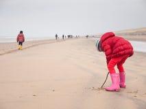 Petite fille jouant sur la plage d'hiver Images libres de droits
