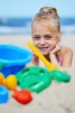 Petite fille jouant sur la plage de sable Photographie stock libre de droits