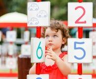 Petite fille jouant sur le terrain de jeu Photo stock