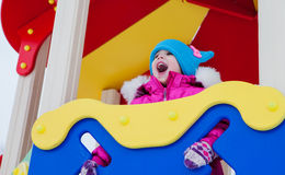 Petite fille jouant sur le terrain de jeu, ayant l'amusement jouant tournant le jour de l'hiver sur la rue dans le parc Image stock