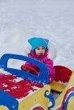 Petite fille jouant sur le terrain de jeu, ayant l'amusement jouant tournant le jour de l'hiver sur la rue dans le parc Photographie stock libre de droits