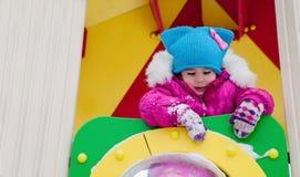 Petite fille jouant sur le terrain de jeu, ayant l'amusement jouant tournant le jour de l'hiver sur la rue dans le parc Images stock