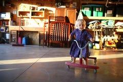 Petite fille jouant sur le tour sur le scooter dans le garage Photos libres de droits
