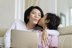 Petite fille jouant un ordinateur portable avec sa mère Photographie stock