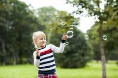 Petite fille jouante blonde avec des bulles de savon dans le pair vert d'été Images stock