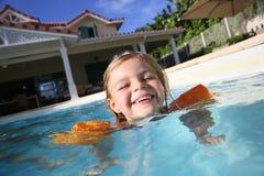 Petite fille joyeuse dans la piscine ayant l'amusement Photos stock