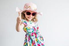 Petite fille joyeuse heureuse souriant montrant des pouces  Photos stock