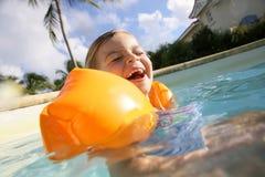 Petite fille joyeuse jouant dans la piscine Images stock