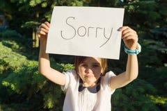 Petite fille jugeant le papier blanc avec le message désolé image stock