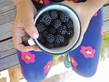 Petite fille jugeant une tasse pleine des mûres mûres photographie stock