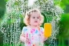 Petite fille lavant une fenêtre Photos stock