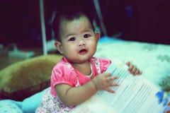 Petite fille lisant peu de livre sur le lit Images stock