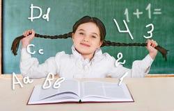 Petite fille lisant un adolescent de sourire de livre près d'un conseil pédagogique Photographie stock