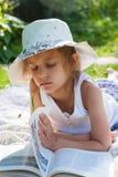 Petite fille lisant un livre dans le jardin Photos stock