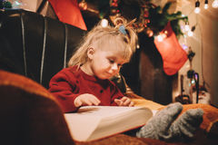Petite fille lisant une histoire pour endormir par la cheminée photos libres de droits