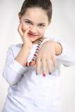 Petite fille lui affichant les clous colorés Image stock