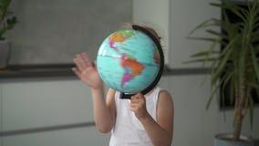 Petite fille méconnaissable tourbillonnant un globe à la maison clips vidéos