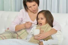 Petite fille malade avec la mère Photographie stock