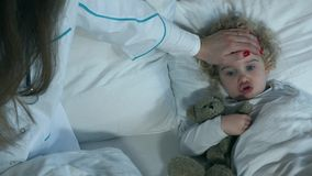 Petite fille malade avec le jouet aimé se trouvant tandis que docteur d'infirmière prenant la température banque de vidéos